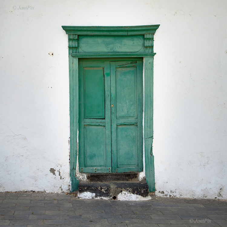 A dilapidated green wooden door in avery old house in Teguise market town in Lanzarote
