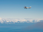 A tourist airplane flies over the Cook Inlet, Alaska towards Lake Clark National Park.