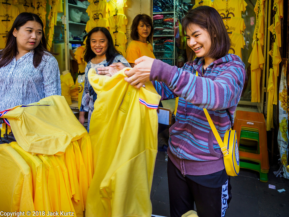 "03 JULY 2018 - BANGKOK, THAILAND: A girl looks at shirts that say ""Long Live the King"" at a shop in Bobae Market. The birthday of King Maha Vajiralongkorn Bodindradebayavarangkun, Rama X, is 28 July. The King, the only son of Thailand's late King Bhumibol Adulyadej, became the King of Thailand in 2016 after the death of his father. King Vajiralongkorn was born on 28 July 1952, a Monday. In Thai culture each day of the week has a color, and yellow is the color is associated with Monday, so people wear yellow for the month before his birthday to honor His Majesty.    PHOTO BY JACK KURTZ"