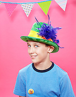 Tween boy wearing a green top hat with a purple feather on a pink seamless. Photographed at the Photoville Photo Booth September 20, 2015