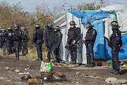 Licensed to London News Pictures. Calais, France. 03/03/16. French riot police stand between the media and demolition teams clearing the 'Jungle' camp. French authorities are clearing the southern half of the Calais 'Jungle' camp, which charities estimate to contain 3,500 people.. Photo credit : Rob Pinney/LNP