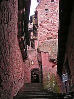 View up steps to a narrow alleyway leading to a stunning, red-brick medieval castle in Alsace, France.