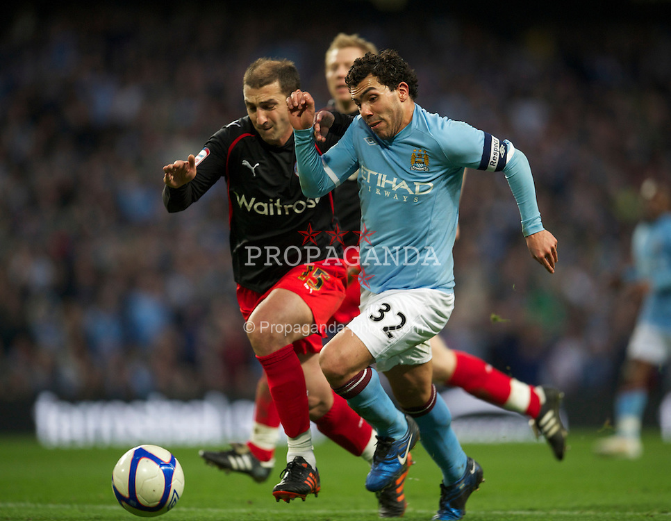 MANCHESTER, ENGLAND - Sunday, March 13, 2011: Manchester City's Carlos Tevez and Reading's Zurab Khizanishvili during the FA Cup 6th Round match at the City of Manchester Stadium. (Photo by David Rawcliffe/Propaganda)
