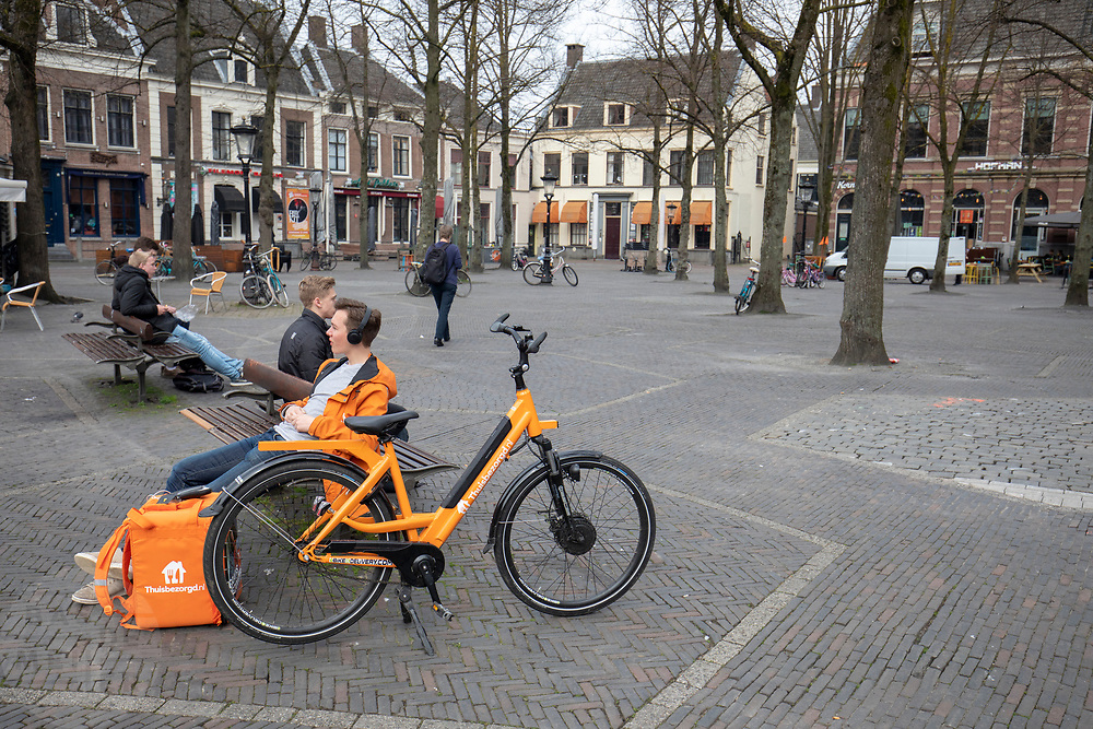 Een bezorger van thuisbezorgd.nl wacht op een bankje op het Janskerkhof in Utrecht op een order.<br /> <br /> A messenger of thuisbezorgd.nl is waiting on a bench for an order at the Janskerkhof in Utrecht.