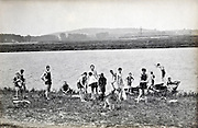 large group swimming by the river early 1900s