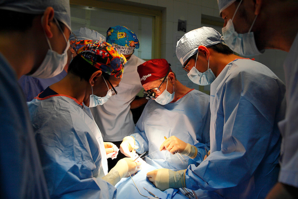 Operation Smile founder Bill Magee lead surgical team during operating to repair a universal cleft on a 6 month year old girl. Hanoi. Vietnam. November 2014<br />