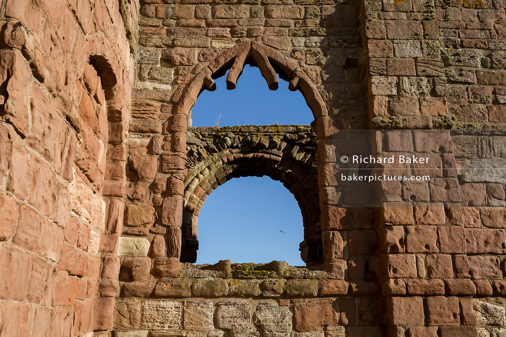 The ruined monastery walls of Lindisfarne priory on Holy Island, on 27th June 2019, on Lindisfarne Island, Northumberland, England. The monastery of Lindisfarne was founded by Irish monk Saint Aidan, and the priory was founded before the end of 634 and Aidan remained there until his death in 651. The Holy Island of Lindisfarne, also known simply as Holy Island, is an island off the northeast coast of England. Holy Island has a recorded history from the 6th century AD; it was an important centre of Celtic and Anglo-saxon Christianity. After the Viking invasions and the Norman conquest of England, a priory was re-established.