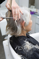 Stylist cuts elderly woman's hair