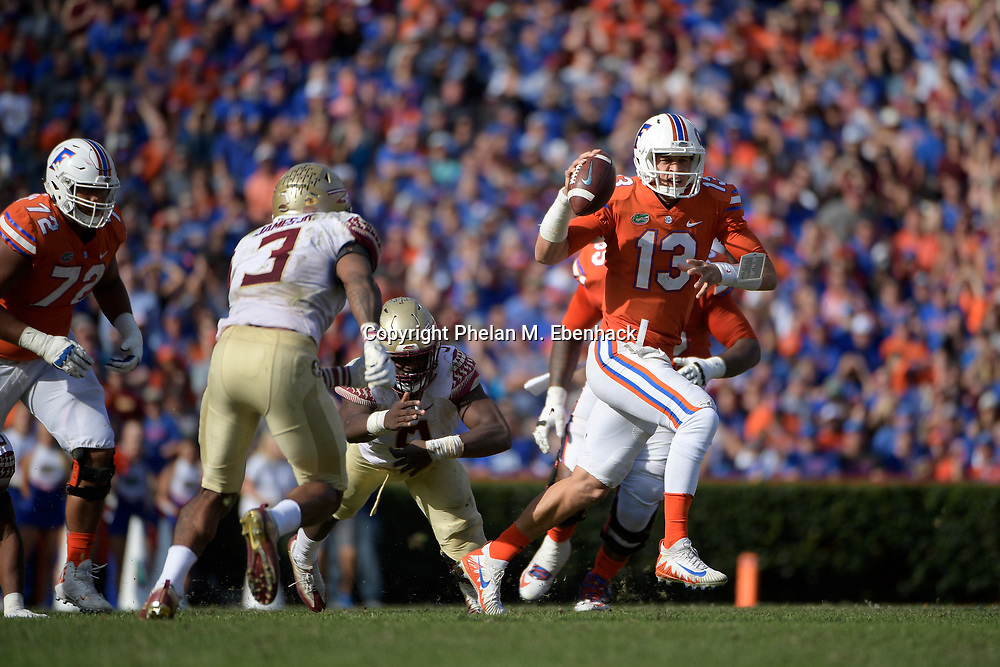 Florida quarterback Feleipe Franks (13) scrambles for yardage in front of Florida State defensive back Derwin James (3) during the second half of an NCAA college football game Saturday, Nov. 25, 2017, in Gainesville, Fla. FSU won 38-22. (Photo by Phelan M. Ebenhack)
