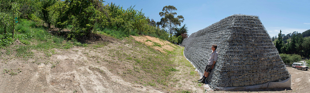Peter McGrail's Gabion Wall built at his orchard in Horotane Valley, to protect a building site where a new home is to be built from any future earthquake triggered rockfalls,  Christchurch, New Zealand, January 12, 2016. Credit: SNPA / David Alexander.