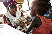 Counselor from UNICEF partner NGO Femme Active Cecile Traore performs a HIV screening test on a young girl at the Koumassi general hospital in Abidjan Cote d'Ivoire on Friday July 19, 2013. The girl tested negative.