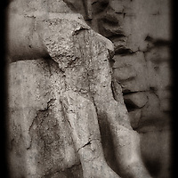 A black and white creative photograph of a ruined statue of an unknown person. Karnak Temple, Egypt.