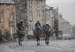 © Licensed to London News Pictures. 22/03/2014<br /> <br /> Middleham, North Yorkshire<br /> <br /> Race horses and their riders make their way through heavy morning snow on their way to exercise at first light on the gallops in Middleham, North Yorkshire. Race horses have been trained in Middleham for over 200 years using the extensive gallops on the high moor. There are currently 15 stables based around the small Yorkshire village.<br /> <br /> Photo credit : Ian Forsyth/LNP