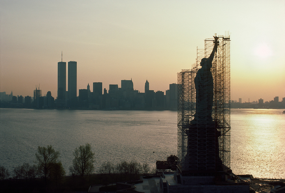 Statue of Liberty being repaired with scaffolding,  and Twin Towers and Lower Manhattan, World Trade Center at Sunrise, New York City, New Jersey,  New York, A centennial conservation-restoration of the Statue of Liberty (Liberty Enlightening the World) occurred between 1984 and 1986
