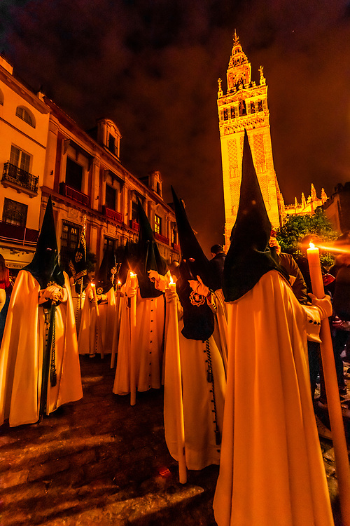 Hooded Penitents (Nazarenos) in the procession of the Brotherhood (Hermandad) La Macarena, early morning on Good Friday, Holy Week (Semana Santa), Seville, Andalusia, Spain.