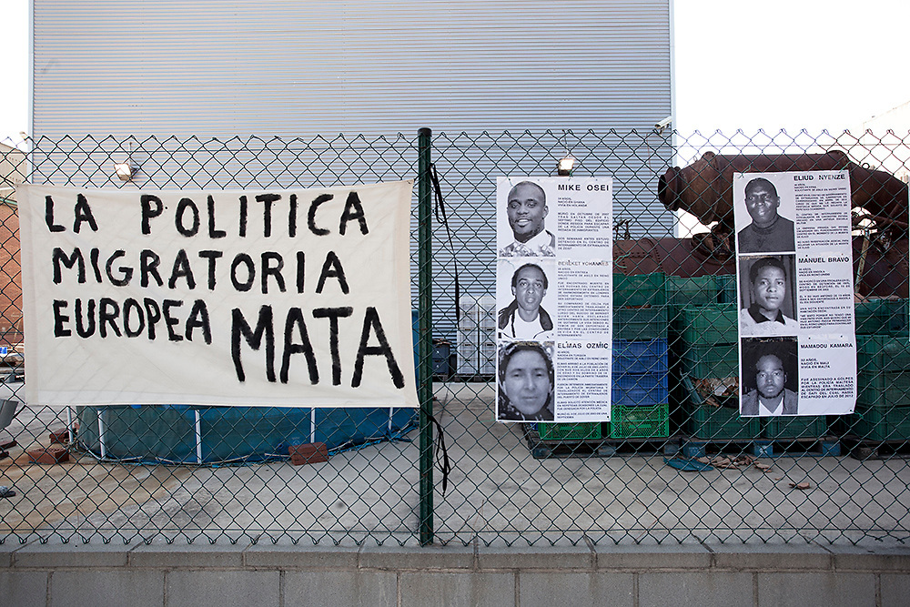 """A cartel shows the photos of immigrants who died under detention in various European countries, either by committing suicide or being beaten to death by the police during the protest organized by""""Tancarem el CIE"""" to get to government to close the Immigration detention center permanently.   Barcelona 20/06/2015"""
