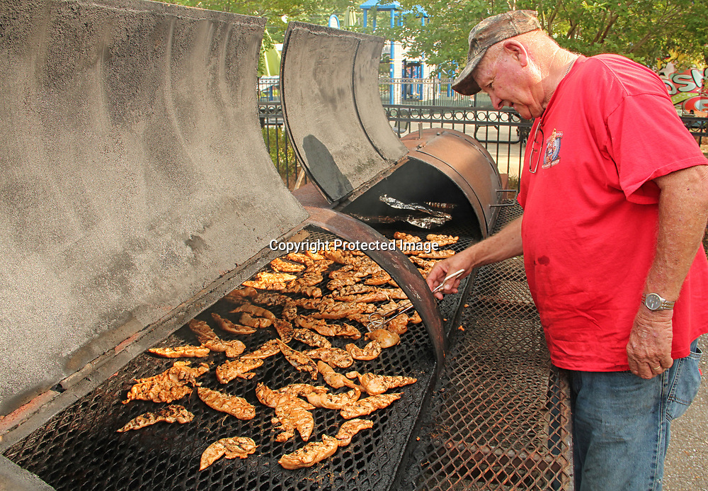 ADAM ARMOUR I BUY AT PHOTOS.ITAWAMBATIMES.COM<br /> Larry Cromeans checks the chicken he's grilling as part of the Itawamba County Development Council's fundraising barbecue plate sale, held during downtown Fulton's Bluegrass, Blues &amp; BBQ Festival, this weekend.