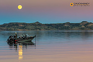 Fishing boat with full moonrise over Fort Peck Reservoir in the CM Russell National Wildlife Refuge near Fort Peck, Montana, USA MR