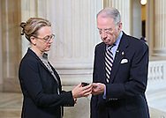 Senator Chuck Grassley (R-IA) looks at a cell phone with then Communications Director and current Chief of Staff Jill Kozeny before an interview on Fox Business Network in the Russell Senate Office Building rotunda in Washington, DC on Wednesday, April 10, 2013.