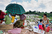 09 NOVEMBER 2004 - TAPACHULA, CHIAPAS, MEXICO: A woman and her child watch a family eat lunch in the municipal garbage dump in Tapachula, Chiapas, Mexico. About 130 people, the poorest of the poor in Tapachula, work in the dump picking through the garbage hoping to find tidbits they can use or sell to brokers who sit on the edge of the dump and resell the garbage. Most of the dump workers are Guatemalan migrants who crossed the border hoping, at one time, to get to the United States. Now they have settled for an existence on the very edge of Mexican society. PHOTO BY JACK KURTZ
