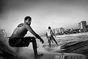 Three surfers ride a wave off the shore of Gaza City, Gaza Strip.