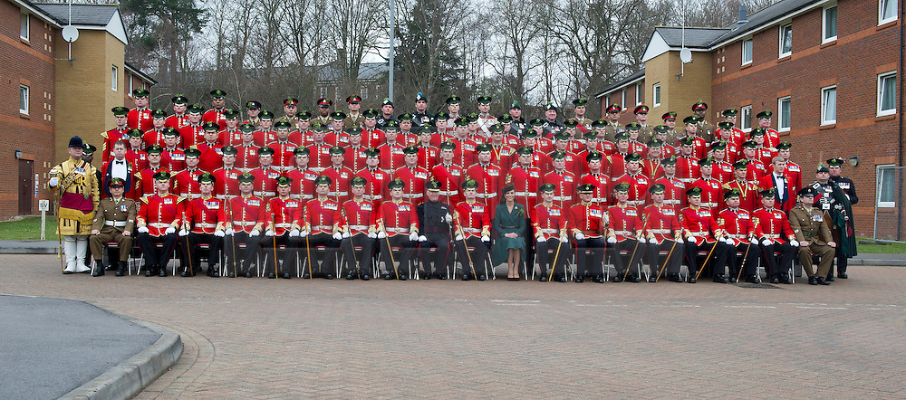 HRH The Duchess of Cambridge sits for a formal group photograph after presenting shamrocks to members of 1 Irish Guards at Mons Barracks in Aldershot today (17 Mar 2012) to mark the occasion of St Patricks Day. ..During the ceremony HRH was presented a shamrock by the QM Major John Mateer which then precluded a parade and a posy presentation by daughter of Drill Sergeant Stevenson, Isabella (5)..NOTE TO DESKS: .MoD release authorised handout images. .All images remain crown copyright. .Photo credit to read - Sergeant Alison Baskerville RLC