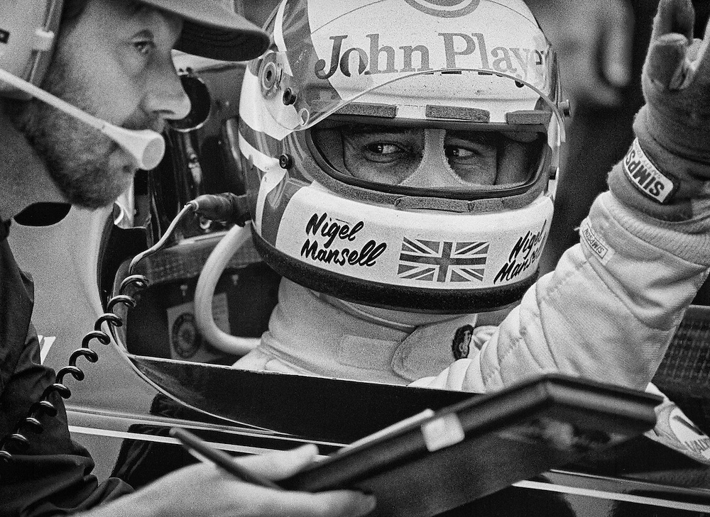 Great Britain's Lotus F1 driver Nigel Mansell listens to pre-race instructions before the start of the 1982 Detroit Grand Prix. <br /> <br /> Mansell began as a test driver for the Lotus Formula One team and graduated to full-time seat in 1981. the season's following the failure of several Lotus F1 designs nearly crippled the team, and Mansell experienced 11 mechanical retirements in his first 23 races. The Detroit Grand Prix would be the 12th. <br /> <br /> When Chapman died unexpectedly in December, 1982, Mansell would experience tremendous pressure and resistance within Lotus from new team manager Peter Warr. There were rumors that Warr had no intention of honoring the last year of Mansell's contract agree to before Chapman's death. And, with rising star Ayrton Senna rumored to be moving to the team, Mansell was desperate for outstanding results. Unfortunately, the Lotus 95T continued to be unreliable. Fortunately, Mansell had developed a great friendship with journalist Peter Windsor.<br /> <br /> When Windsor accepted a position with Williams F1 to managing their sponsorship and public affairs in 1985, and his timely words to Frank Williams seemed to make a difference. Mansell joined Williams that same year and began to rebuild his career. He would win his first Grand Prix, the European Grand Prix at Brands Hatch, England, and defeat Ayrton Senna's Lotus in the process and match it with the a victory in the South African grand Prix 13 days later. <br /> <br /> Mansel would go on to finish 2nd in the World Driver's Championship three times with Williams and Ferrari, finally winning the World Championship in a triumphant nine-victory return season with Williams in 1992.<br /> <br /> In all, 31 victories; the most Grand Prix wins by a British Formula One driver of all time. He was appointed Commander of the British Empire in 2012.