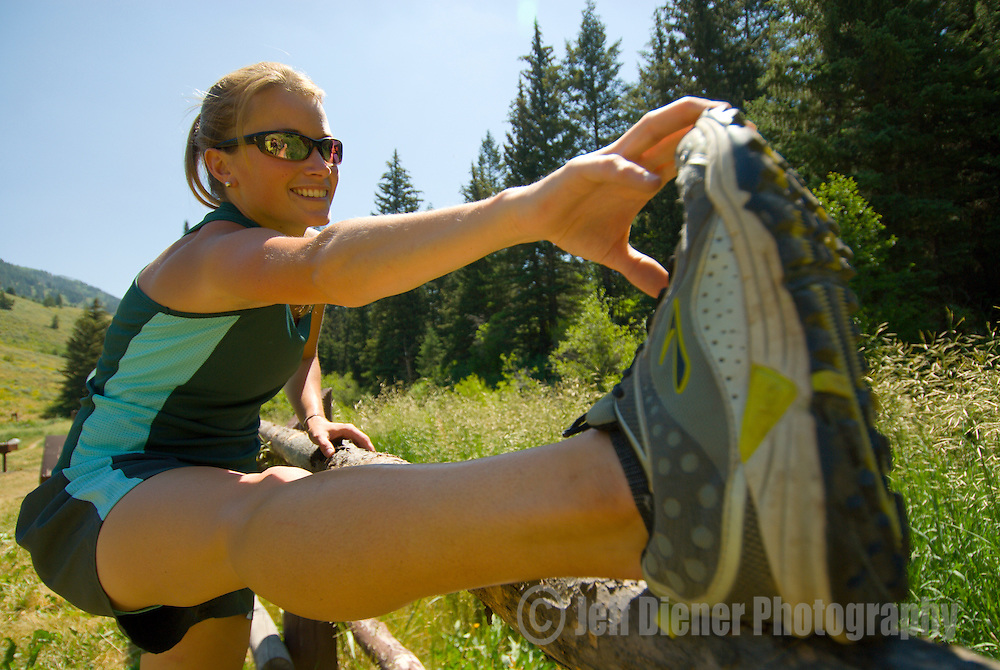 A young woman stretches before going trail running in Jackson Hole, Wyoming.