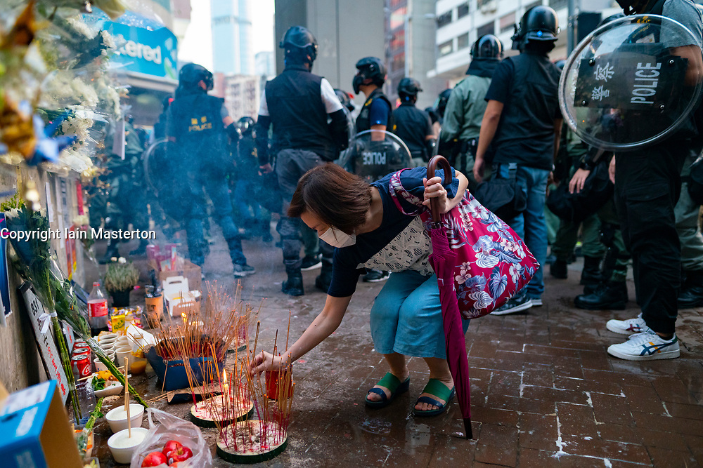 Hong Kong, China. 12th October 2019. Peaceful Pro-democracy march from tourist district of Tsim Sha Tsui along busy Nathan Road to Sham Shui Po Park in Kowloon. Some minor acts of vandalism to property were recorded but most marchers acted peacefully. Evening saw vigil at shrine at Prince Edward MTR  for protestor who died in police custody. Woman lighting incense at shrine surrounded by riot police. Iain Masterton/Alamy Live News.