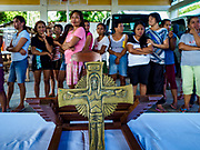 21 JANUARY 2018 - CAMALIG, ALBAY, PHILIPPINES: People line up behind a crucifix for relief supplies at the Barangay Cabangan evacuee shelter in a school in Camalig. There are about 650 people living at the shelter. They won't be allowed to move back to their homes until officials determine that Mayon volcano is safe and not likely to erupt, which could take at least two more weeks. More than 30,000 people have been evacuated from communities on the near the Mayon volcano in Albay province in the Philippines. Most of the evacuees are staying at schools in communities outside of the evacuation zone.   PHOTO BY JACK KURTZ
