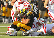November 02 2013: Iowa Hawkeyes running back Jordan Canzeri (33) is pulled down by Wisconsin Badgers safety Michael Caputo (7) and Wisconsin Badgers linebacker Ethan Armstrong (36) during the second half of the NCAA football game between the Wisconsin Badgers and the Iowa Hawkeyes at Kinnick Stadium in Iowa City, Iowa on November 2, 2013. Wisconsin defeated Iowa 28-9.