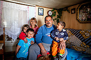 "Portrait of Marian with his family in in their house located at the Roma settlement  Ostrovany in East Slovakia. Marian: ""We are devided (by the fence) - into white and the gypsies. When there was no fence some of the people stole just some fruits and vegetables. The ""Berlin Wall"" does not matter for us anymore, standing there already a few years. They were building it well."" In 2010, the town of Ostrovany received international media attention when the town council built a wall dividing private gardens and the neighboring Roma settlement. Several media outlets compared the look of Ostrovany's 150 m long wall with the Berlin Wall. Mayor Mr. Rehak sees the building as a ""fence"" and not a wall."