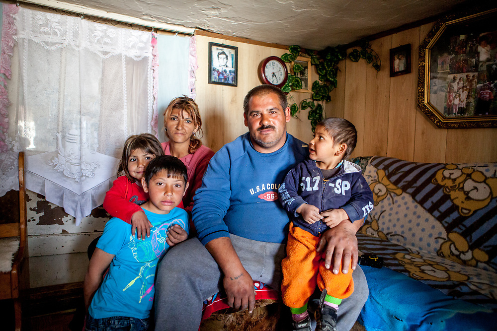 """Portrait of Marian with his family in in their house located at the Roma settlement  Ostrovany in East Slovakia. Marian: """"We are devided (by the fence) - into white and the gypsies. When there was no fence some of the people stole just some fruits and vegetables. The """"Berlin Wall"""" does not matter for us anymore, standing there already a few years. They were building it well."""" In 2010, the town of Ostrovany received international media attention when the town council built a wall dividing private gardens and the neighboring Roma settlement. Several media outlets compared the look of Ostrovany's 150 m long wall with the Berlin Wall. Mayor Mr. Rehak sees the building as a """"fence"""" and not a wall."""