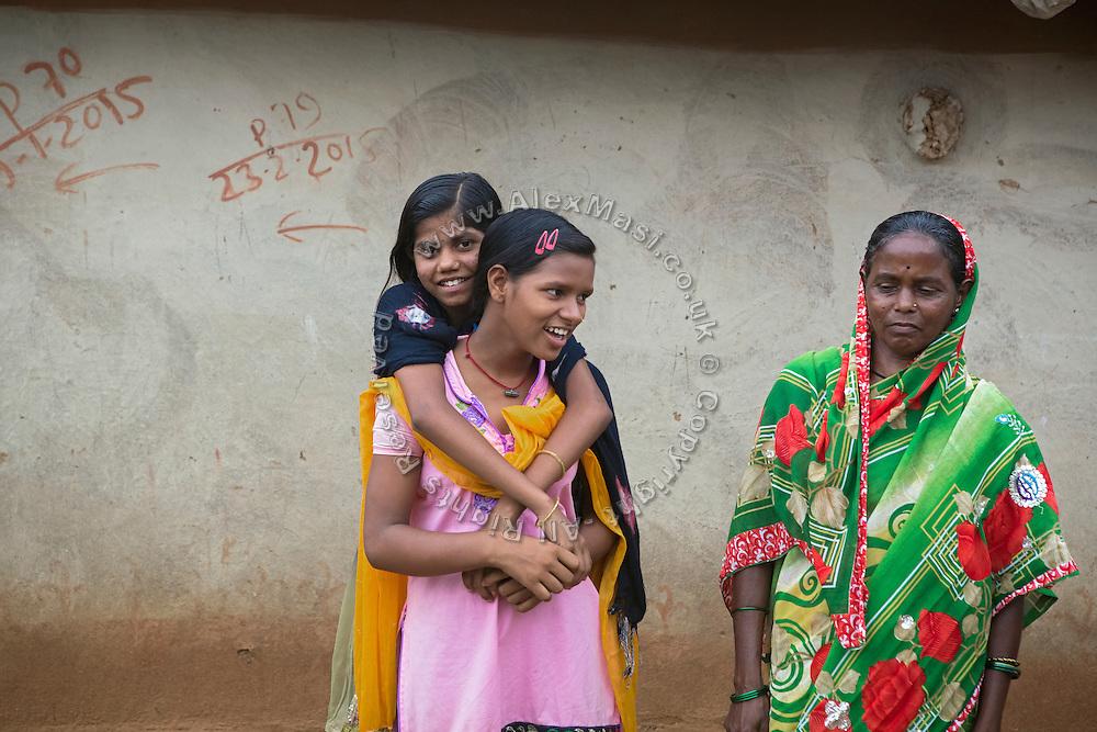 Standing next to her mother Kitabun Bibi, 45, (right) Tabasum Khatun, 14, is embracing her best friend - and partner of Karate classes - Anju Kumari, 13, (front) in Algunda village, pop. 1000, Giridih District, rural Jharkhand, India.