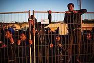 Lampedusa, Italia - 22 marzo 2011. Immigrati nordafricani si ammassano lungo una cancellata della stazione marittima di Lampedusa per ricevere un pasto caldo.Quasi 6000 immigrati ospitati tra il centro di accoglienza temporanea dell'isola e la stazione marittima..Ph. Roberto Salomone Ag. Controluce