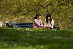 London, April 25th 2015. Despite the threat of forecasted showers, spring sunshine and warmth greets Londoners as they enjoy the Royal Parks in the capital. PICTURED: Two women enjoy the dappled shade in Green Park.