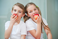 Portrait of young boy and girl in white tshirts eating apples