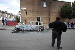 © Licensed to London News Pictures . FILE PICTURE DATED 07/08/2011 . Tottenham , UK . A woman with her hands on her hips looks on at a burned out people carrier on Pembury Road in Tottenham following a night of rioting . The following night the Pembury Estate , 3.5 miles away in Hackney , saw some of the worst rioting of the Summer . Photo credit : Joel Goodman/LNP