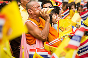 05 DECEMBER 2012 - BANGKOK, THAILAND: A Buddhist monk surrounded by Thai blows a conch to announce the impending arrival of the King on the Royal Plaza Wednesday. They were all waiting to see Bhumibol Adulyadej, the King of Thailand, before his public audience at the Mukkhadej balcony of the Ananta Samakhom Throne Hall. December 5 is a national holiday. It's also celebrated as Father's Day. Celebrations are being held across the country to mark the birthday of Bhumibol Adulyadej, the King of Thailand.    PHOTO BY JACK KURTZ