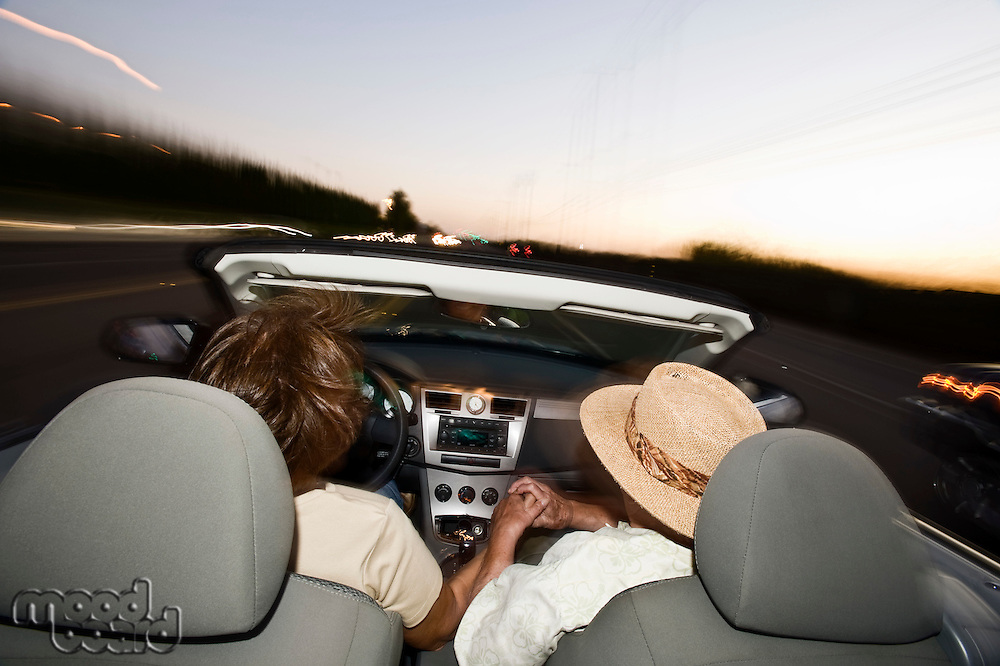 Senior couple driving in convertible on country road at dusk, back view