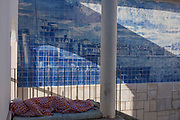 A homeless man sleeps under blankets in front of Azulejo tiles in a city park, Lisbon Portugal.
