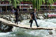 Crossing over a raging river on a precarious wooden slatted bridge in Setti Fatma