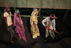 April 28, 2018 - Dhaka, Bangladesh - A labor fills up basket as others wait to deliver on their head from a cargo to a wholesale market at Dhaka. (Credit Image: © Md. Mehedi Hasan via ZUMA Wire)