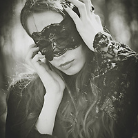 A woman in a black vintage gown, with hidden eyes by black lace, standing, with hands near her face..