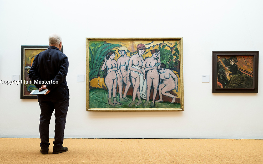 Visitor looking at painting Women Bathing by Ernst Ludwig Kirchner at the  Brücke Museum in Dahlem , Berlin, Germany