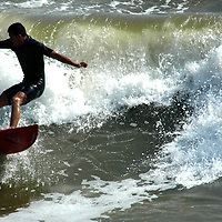 Surfer catches a wave at Santa Monica Beach.