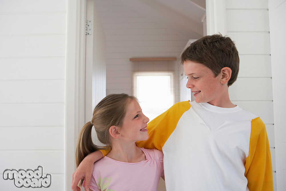 Young boy with arm around girl standing in house half length