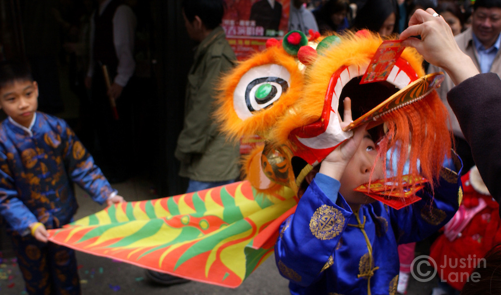 Jason Wong (R) accepts an offering of a red envelope containing money while performing a tradition lion dance to ward off evil spirits with his cousin Nicholas Wang (L) during Chinese New Year celebrations in Chinatown in New York Wednesday 9 February 2005.