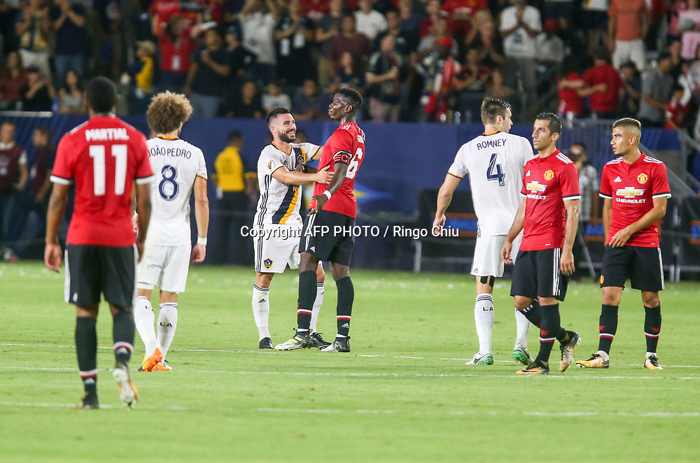 Los Angeles Galaxy midfielder , left, and Manchester United defender  battle for the ball during the second half of a national friendly soccer game at StubHub Center on July 15, 2017 in Carson, California. Manchester United won 5-2. AFP PHOTO / Ringo Chiu