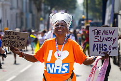 A woman carries placards in support of the NHS as day one, Children's Day, of the Notting Hill Carnival gets underway in London. London, August 25 2019.